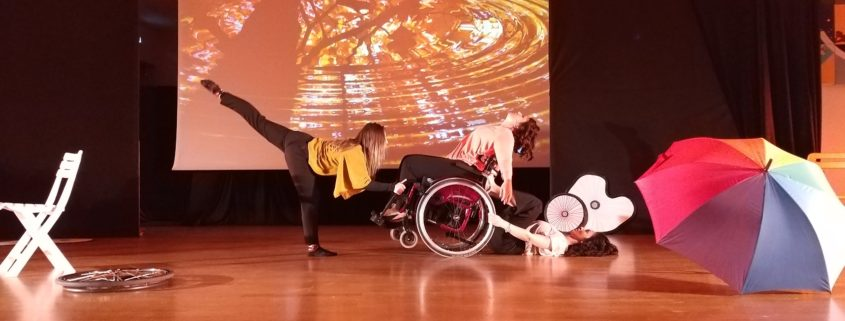 Giovanna Barbero e due sue allieve, di cui quella centrale con disabilità motoria, si esibiscono in una performance di danza.
